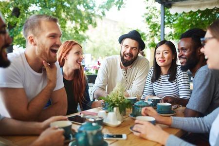 カフェでお茶して話を持ってうれしそうな十代の若者たち