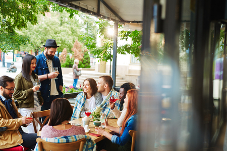 personas dialogando: Grupo de gente amable jóvenes hablando en el café al aire libre Foto de archivo