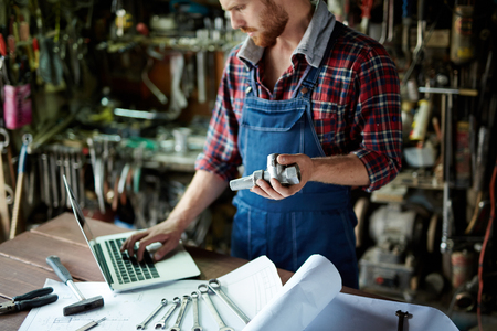 finding out: Mechanic finding out spare parts through the net