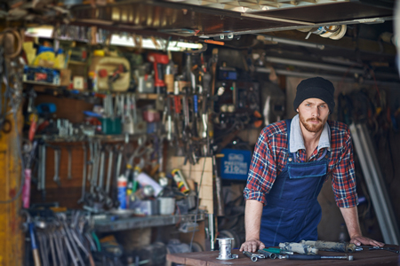Young repairman looking at camera in workshop Stock Photo