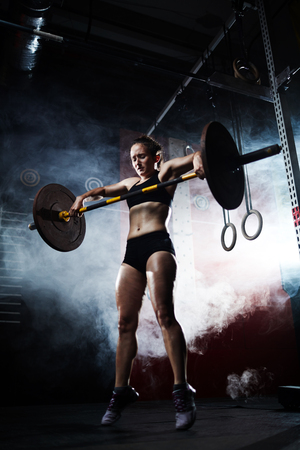 effort: Young woman with weight making effort while lifting it Stock Photo