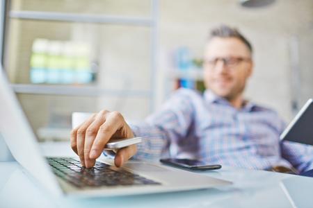 ノート パソコンのキーを押すと携帯電話を持つ男の手
