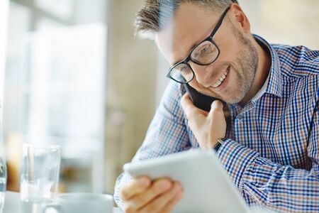 telephony: Happy man in eyeglasses talking on the phone and using touchpad