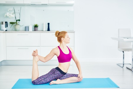 Pretty young woman doing stretching exercise Stock Photo