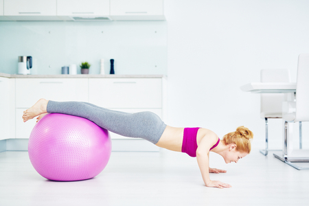 activewear: Girl doing push-ups in the kitchen with her legs on fitball