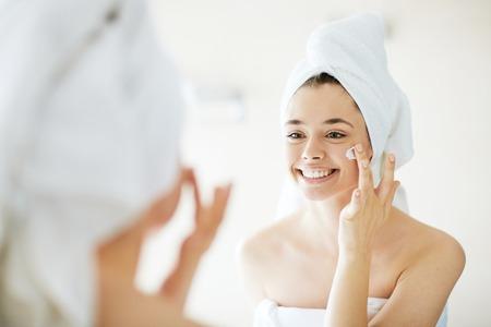 Mujer joven que aplica la crema facial delante del espejo