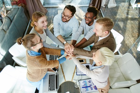altogether: Happy people making pile of hands over workplace in office
