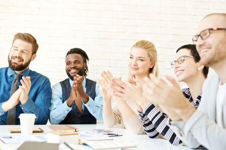 Gruppe zufriedener Manager Sprecher nach der Präsentation applaudieren