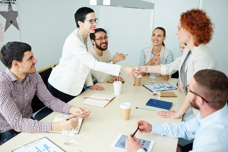 congratulating: Two businesswomen congratulating one another by handshake Stock Photo