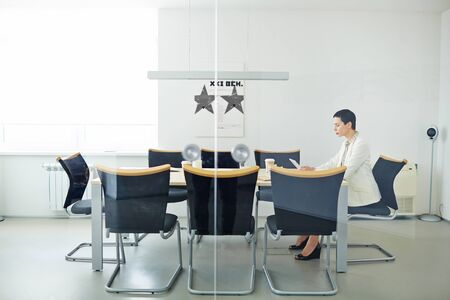 busy person: Serious businesswoman with touchpad sitting in office by table