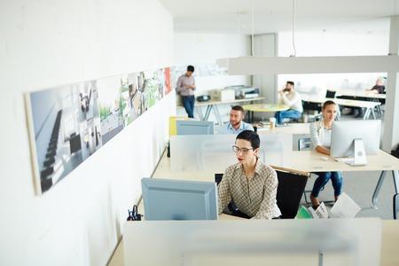 オープン スペースのオフィスで彼女の職場でコンピューティング現代実業家