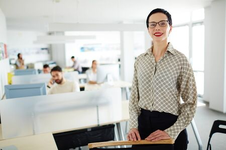 openspace: Successful employer looking at camera on background of working managers