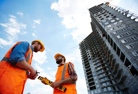 inspectors: Modern inspectors talking by new building on construction site Stock Photo