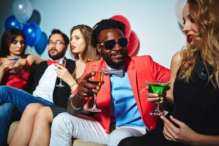 Intercultural couple with drinks talking at party Stock Photo