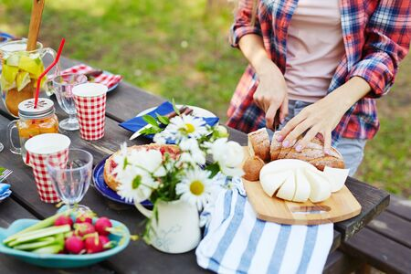 picnic table: Young woman cutting bread and cheese for dinner Stock Photo