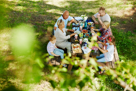 grandkid: Family members sitting around wooden table and having dinner
