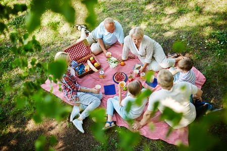Three generations having lunch on the ground