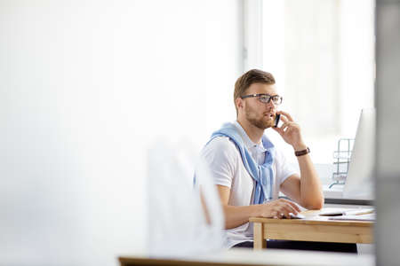 work addicted: Busy employer calling on cellphone while computing at workplace