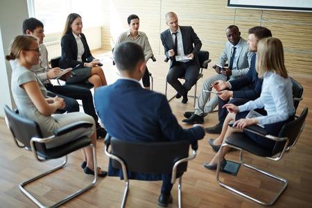 ビジネスマンの説明を聞きながら同僚のグループ