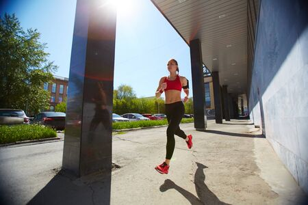 activewear: Fit girl in activewear running in the city