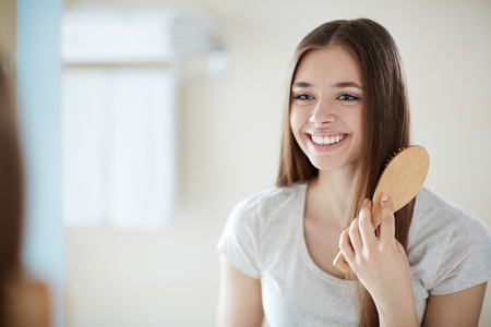 combing: Young lady combing with wooden hairbrush Stock Photo