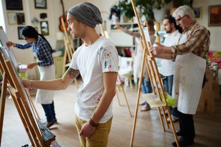 Grupo de estudiantes a pintar a clases de arte Foto de archivo