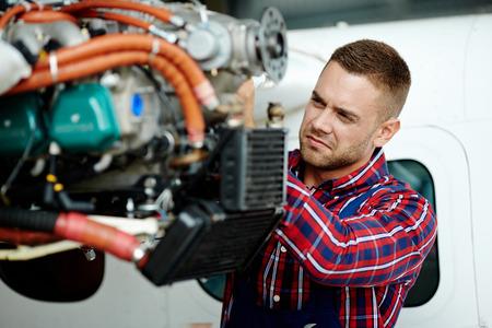 Giovane ingegnere riparazione parte di aeroplano
