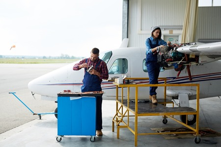 technician: Team of aircraft engineers repairing parts of jet