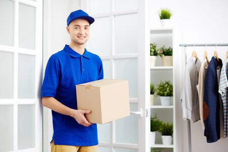courier: Smiling male courier delivering parcel package box