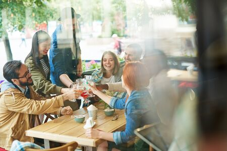 Happy people sitting at the table and toasting Stock Photo