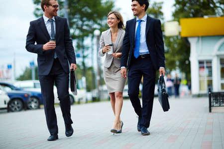 personas en la calle: la gente de negocios feliz de caminar por la calle y que bebe el café para llevar