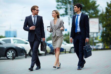 personas en la calle: Los jóvenes empresarios caminando juntos a lo largo de la calle Foto de archivo