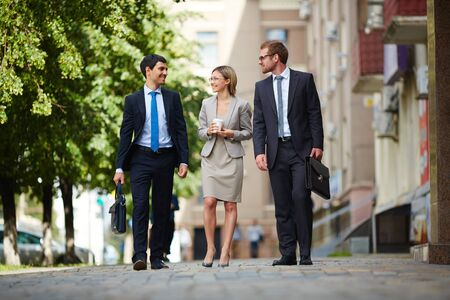 smiling businessman: Successful young business people walking together outdoors Stock Photo
