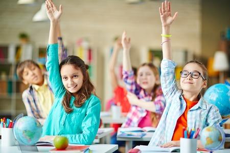 Inteligentny grupa dzieci w wieku szkolnym, podnosząc ręce w odpowiedzi na pytanie,