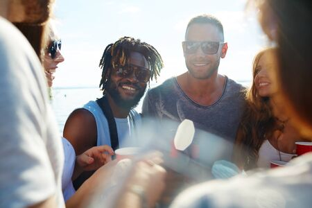 ethnicity: Happy young men in sunglasses spending time outdoors with their friends Stock Photo