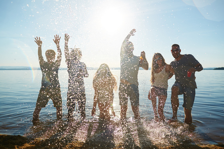 Young people standing in the water and splashing water Stock Photo