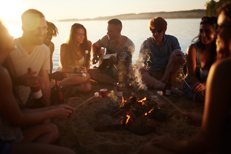 Friends sitting in the sand in circle around a camp fire and singing and a boy is playing guitar Stock Photo