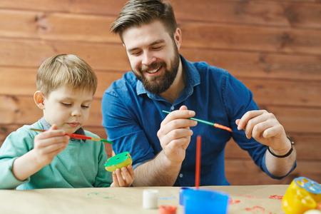 Leuke jongen en zijn vader het creëren van kleurrijke appel postzegels