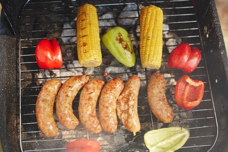 corn meal: Cooked sausages with vegetables on the grill grate