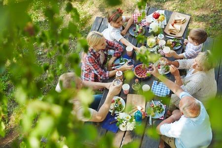La familia feliz con un picnic en el jardín