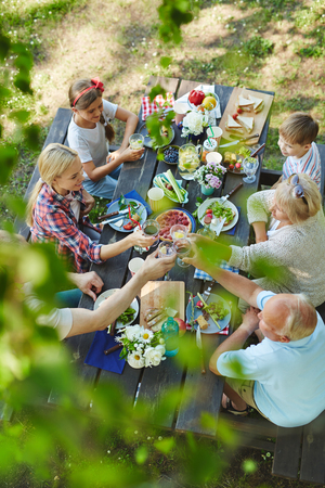 Big happy family with kids and grandparents having healthy tasty bbq lunch outdoors