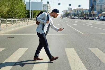 Jonge man met mobiele telefoon spelen augmented reality spel, terwijl het oversteken van de straat