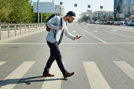 Young man with mobile phone playing augmented reality game while crossing street