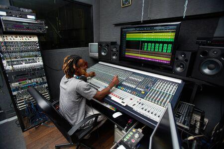 equipo de sonido: Disc jockey sentado en frente de equipo de sonido en el estudio