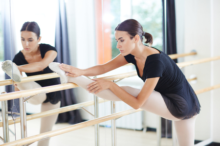 Caucasian girl having repetition of ballet stretching in front of mirror Stock Photo