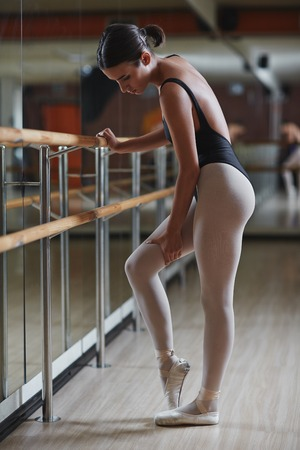 Young female having repetition of ballet exercise in front of mirror