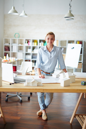 female architect: Female architect looking at camera by workplace Stock Photo