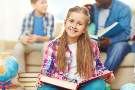 child smile: Happy girl with open book looking at camera