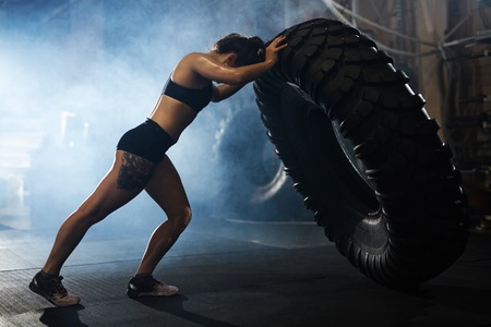 Strong woman flipping tyre in gym