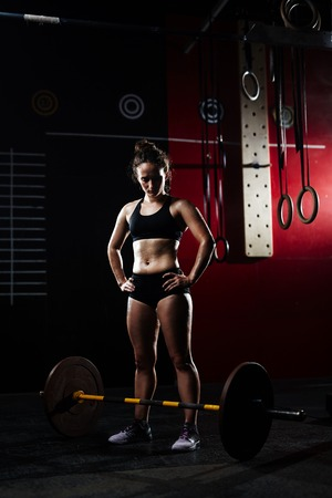 heavy weight: Young woman looking at heavy weight in gym